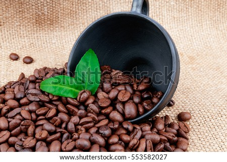 Coffee beans with clay cup & green leaves on wooden