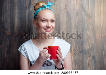 Coffee break. Young attractive smiling woman holding cup of beverage against wooden wall.