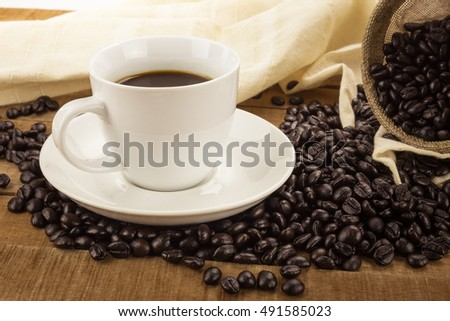 Coffee cup and bag with coffee beans on wooden table
