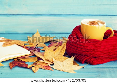 Coffee cup over a scarf, autumn leafs and notebook