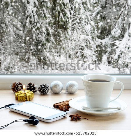 Coffee cup, smartphone, headphones, gifts and Christmas tree ornaments on a windowsill. In the background, a beautiful winter forest in snow