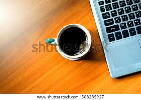 Coffee cup top view on wooden table background and notebook for office.