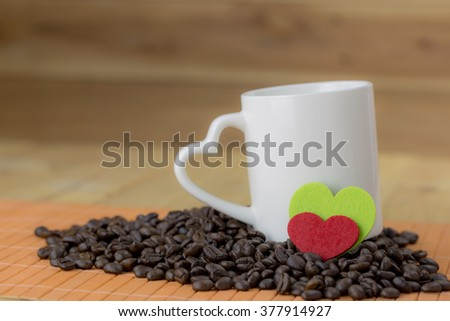 coffee cup with heart shape handle and coffee bean on wood background and cloth red and green  heart