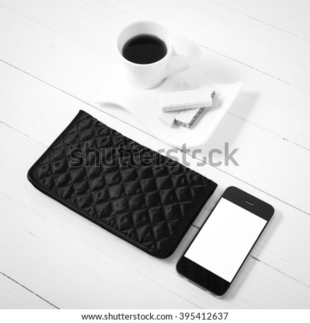 coffee cup with wafer,phone,wallet on white wood background black and white color