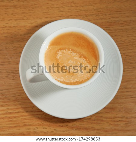 Coffee in a white cup, over wooden table