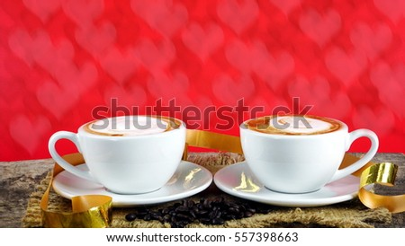 Coffee Lovers. Cups of latte, cappuccino or espresso coffee with milk put on a wood table and red hearts background with dark roasted coffee beans and gold ribbon.