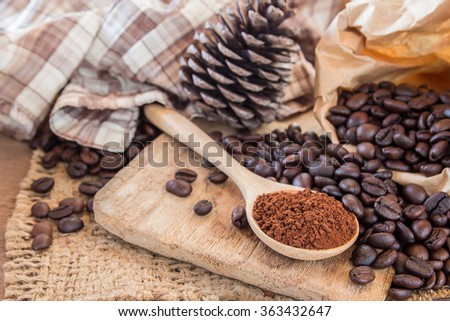 Coffee powder in wooden spoon and coffee beans on wooden table background