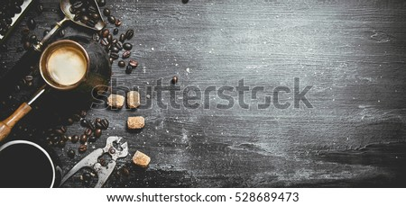 coffee style . Brewed coffee pot with sugar and coffee beans around. On a black chalkboard.