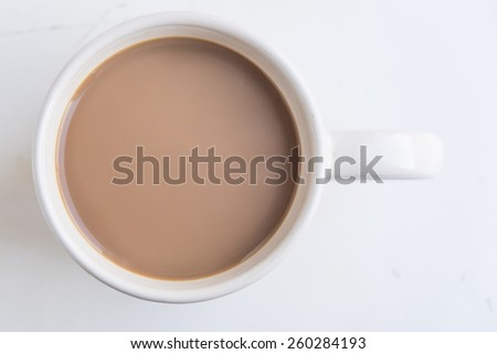 Coffee with milk or cream seen from above