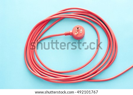 Coiled red electrical cable or lead with a three prong integrated Australian plug on a blue background