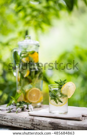 Cold drink of lemon, mint, basil and ice cubes in glass jar