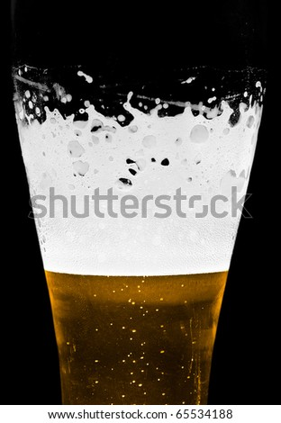 Cold foamy beer in a glass closeup. Studio shot, isolated on black.