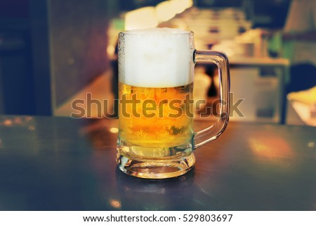 Cold mug of beer with blurred background,beer vintage,glasses of light and dark beer pub