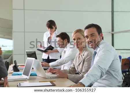 Colleagues working at laptop computers in an office environment