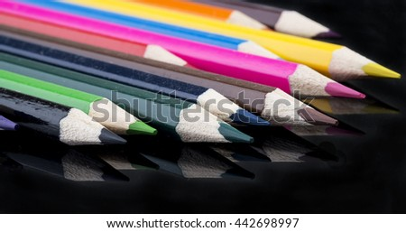 collection of sharp color pencils with reflection on black background
