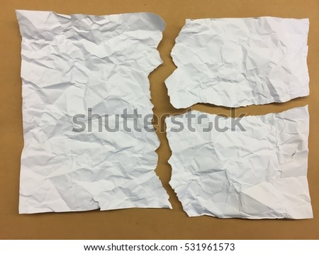 collection of white crumpled ripped pieces of paper on on brown background