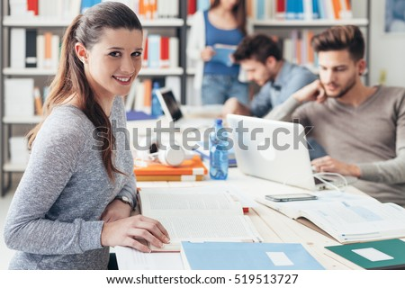 College students sitting at desk and studying together, reading books and using laptops, smiling girl on foreground