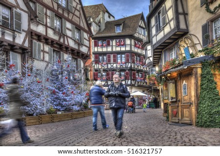 COLMAR,FRANCE-DEC 6: People walking in a town square between traditional half-timber houses and specific Christmas decoration in Colmar, Alsace, France. on December 6, 2013