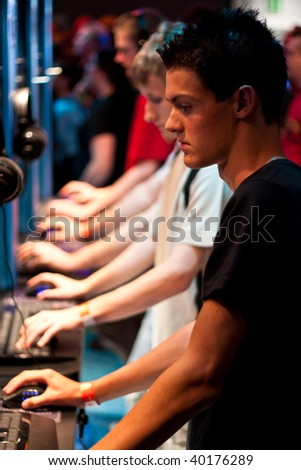 COLOGNE - AUGUST 22: Young video gamers play an online game during GamesCom 2009 August 22, 2009 in Cologne, Germany.