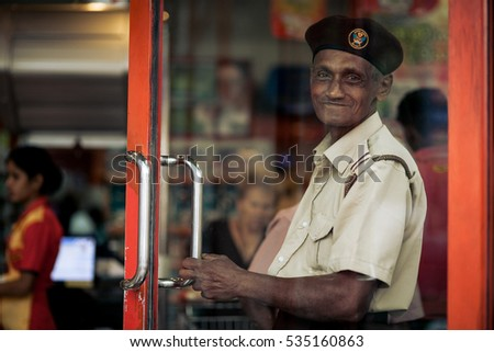 COLOMBO, SRI LANKA - DECEMBER 04, 2016 : Security man at the local supermarket greets customers at the door giving them come in.