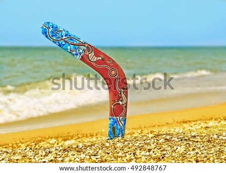 Color Boomerang on Sandy Beach Against of Azure Sea Surf.
