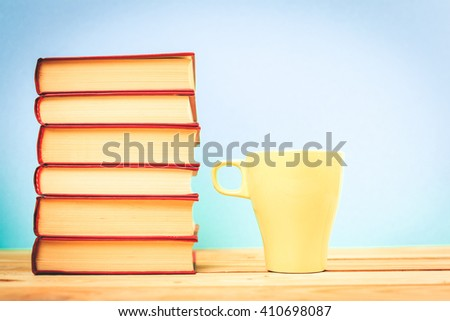 Color cup of tea with books on table