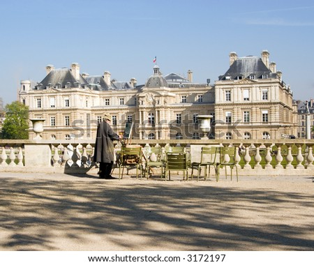 Color DSLR image of unrecognizable man painting a picture of the Palais du Luxembourg, Paris, France.  Gardens are a popular Left Bank, Latin Quarter spot for artists, tourists and locals.