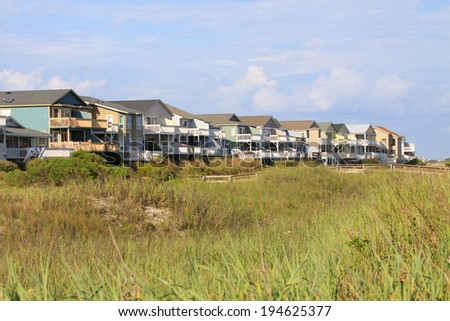Color DSLR luxury beach vacation houses along the green grass covered sand dunes; in Sunset Beach, North Carolina.  The image is in horizontal orientation with ample copy space for text