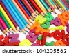 Color pencils and magnets on white paper - stock photo
