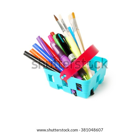 Color pencils, felt-tip pens, markers, brushes and pens in a blue toy basket isolated on a white background. School shopping theme.