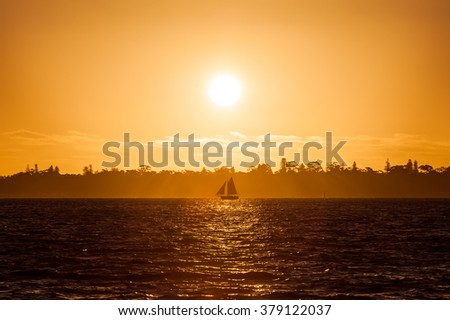 color picture of a sailboat on the river at sunset
