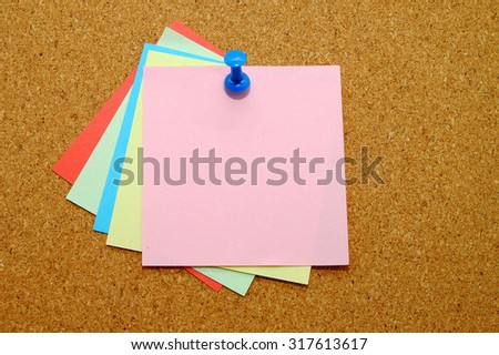 Color sticker notes over cork board background.