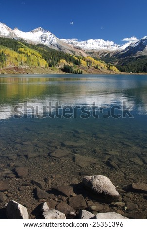 Colorado San Juan Mountains reflecting in tranquil lake with aspens trees in fall