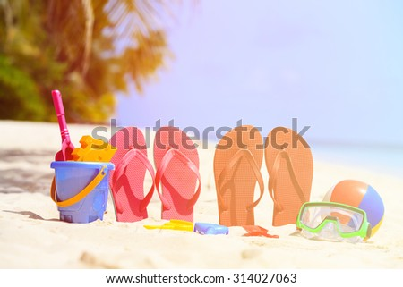 Colored slippers, toys and diving mask at beach, vacation concept