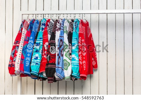 Colored Ukrainian national costumes on a hanger by a white wooden wall