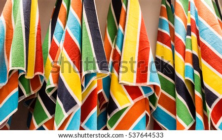 Colorful beach towels hanging on a rack