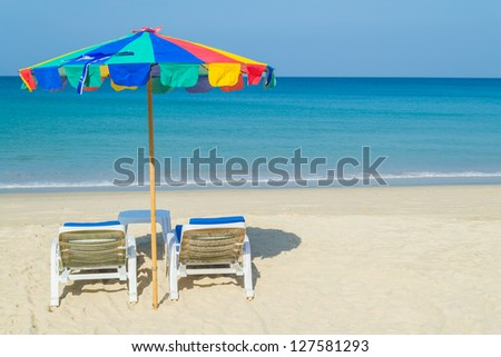 colorful beach umbrella and deck chairs on the tropical beach