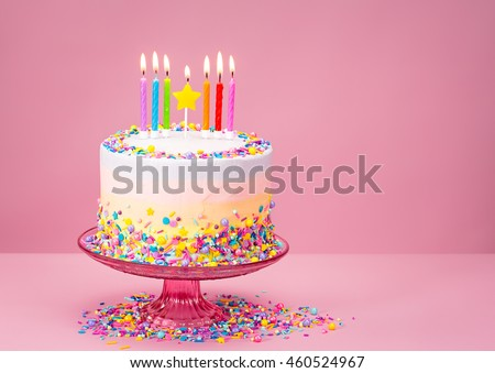 Colorful Birthday cake with sprinkles over a pink background.