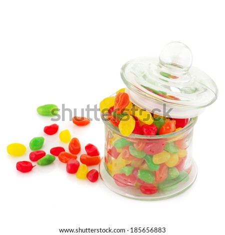 Colorful candied fruits in glass jar isolated on white background.