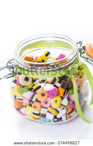 Colorful candies in glass candy jar on a white background.