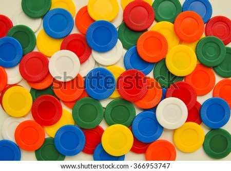 Colorful casino chips from a toy set spread out on a white surface