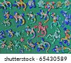 Colorful ceramic lizards over a green background - stock photo