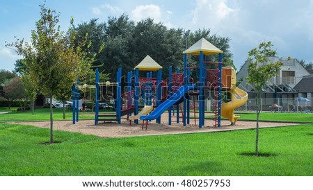 Colorful children playground activities in public park surrounded by green trees in Houston, Texas. Children run, slide, swing on modern playground. Urban neighborhood childhood concept. Panorama.