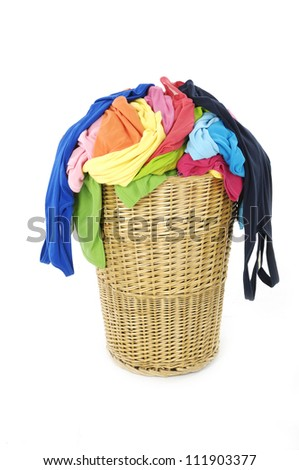 Colorful clothes in a laundry basket on white