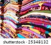 colorful clothes stacked at an Indian market - stock photo