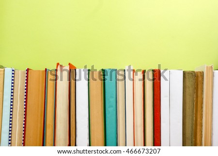 Colorful composition with vintage old hardback books stacking, diary on wooden deck table and green background. Back to school. Copy Space. Education.