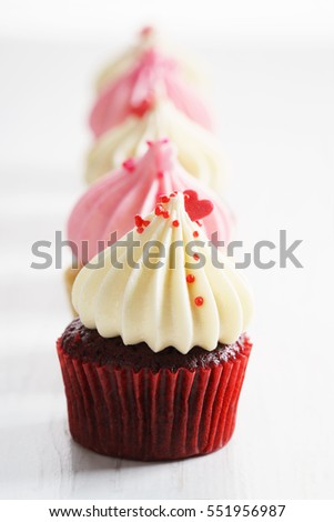 colorful cupcakes, red and pink, with buttercream and heart figure candy. love concept.