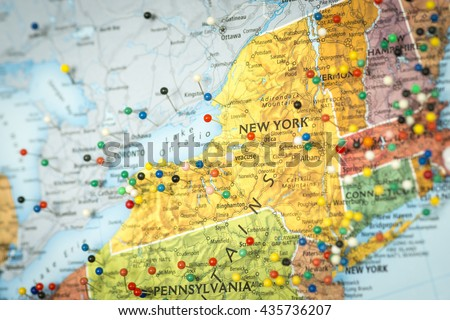 Colorful detail map macro close up with push pins marking locations throughout the United States of America NY New York