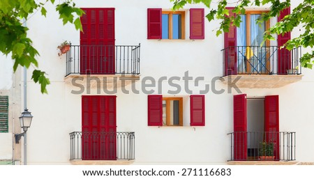 Colorful facade of spanish style old house surrounded by trees.