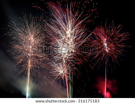 Colorful fireworks exploding in a summer night sky; image composed by four different photos.